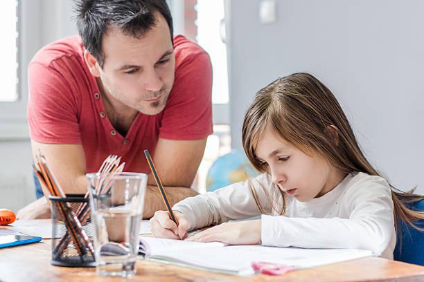 father helping daughter with homework - working from home bildbanksfoton och bilder