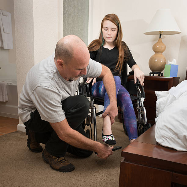 Father helping disabled daughter stock photo
