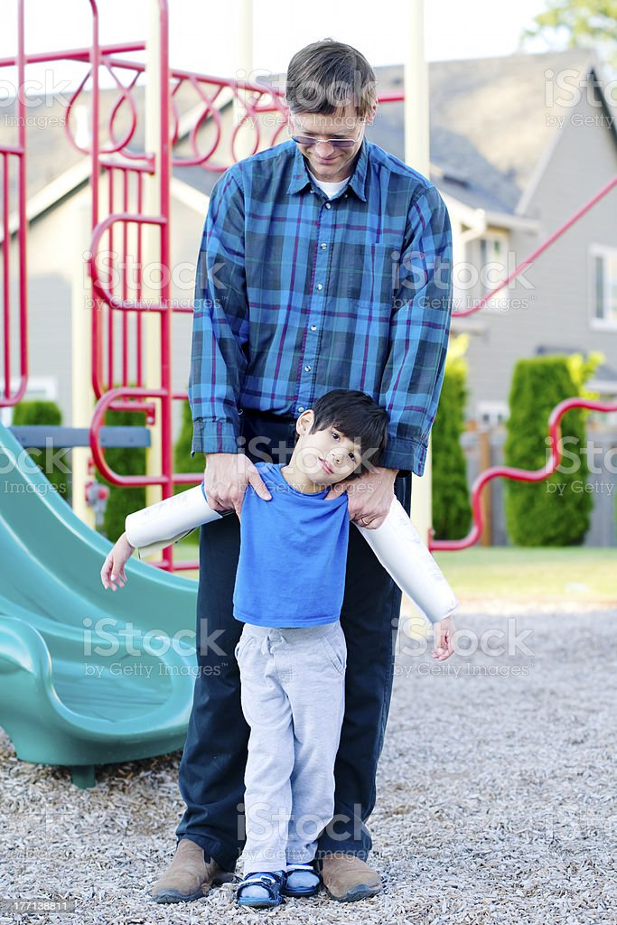 Father helping disabled son at playground royalty-free stock photo