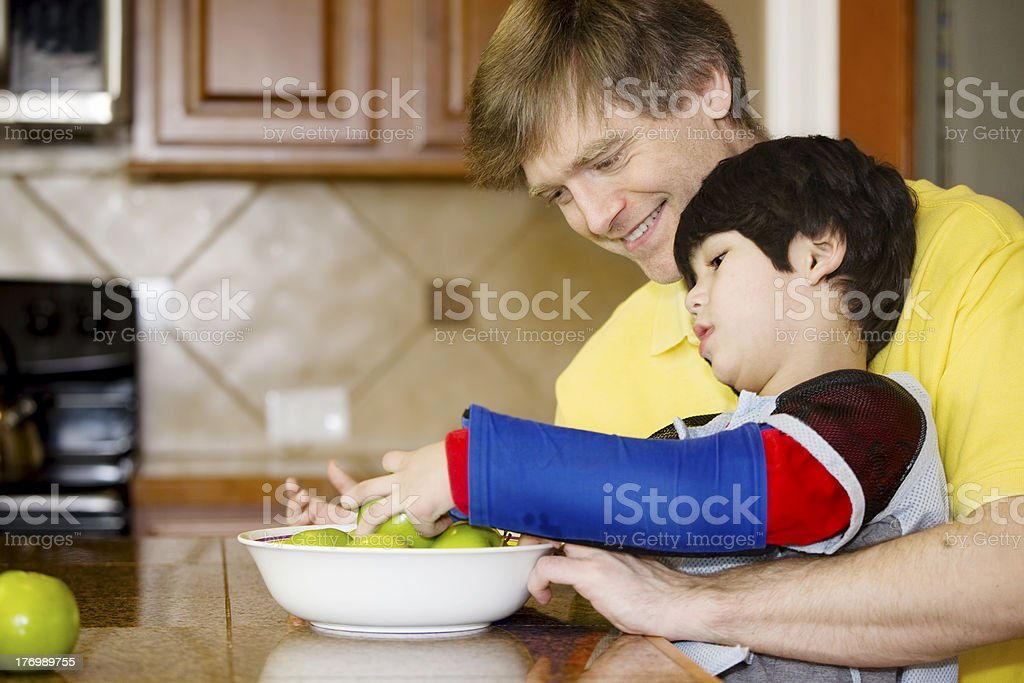 Father helping disabled son with work in the kitchen stock photo