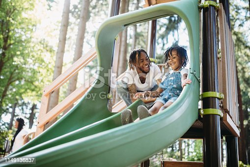 A dad assists his father going down a slide at a public city park in Tacoma, Washington.  They smile and laugh, having fun together in the warm weather.