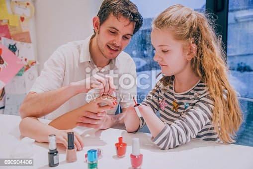 istock Father Helping his Daughter Paint her Prosthetic Limb Nails 690904406