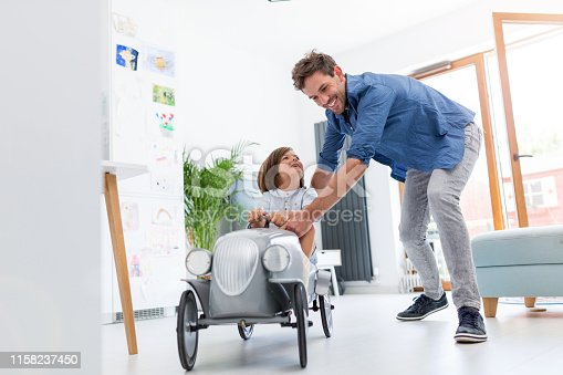 942256562istockphoto Father helping his son to drive a toy peddle car 1158237450