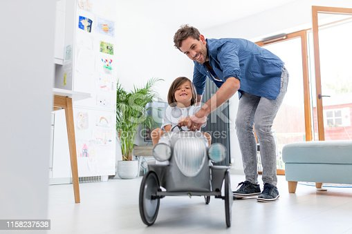 942256562istockphoto Father helping his son to drive a toy peddle car 1158237538