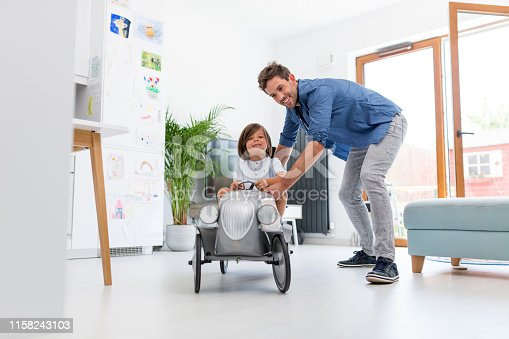 942256562istockphoto Father helping his son to drive a toy peddle car 1158243103