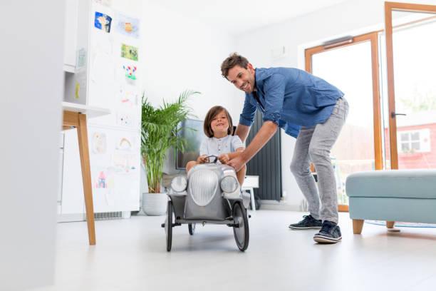 Vater hilft seinem Sohn, ein Spielzeug Hauswagen zu fahren – Foto