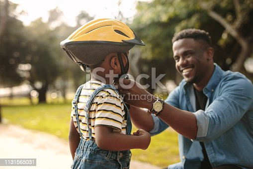 Man helps boy fastens protective helmet for learning to ride bicycle at park. Father helping his son to wear a cycling helmet.
