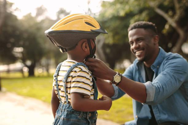 father helping his son to wear a cycling helmet - kask sportowy zdjęcia i obrazy z banku zdjęć