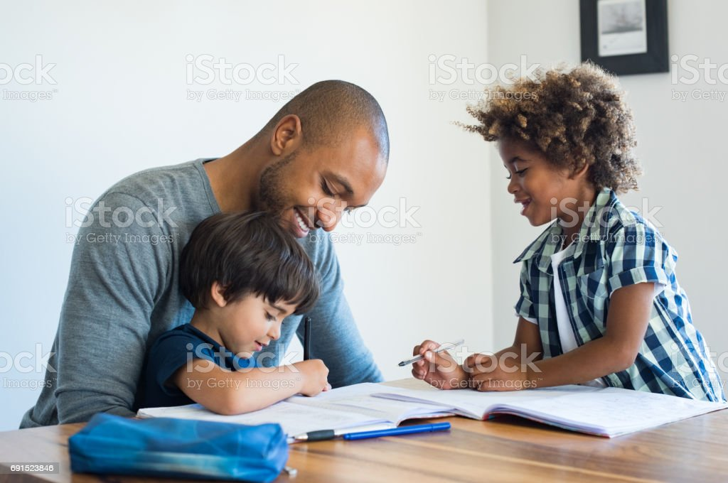 Father helping his sons with homework stock photo
