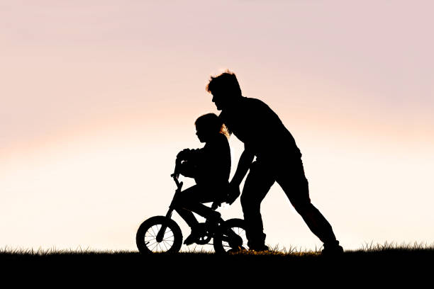 Father Helping his Young Child Learn to Ride Bike with Training Wheels stock photo