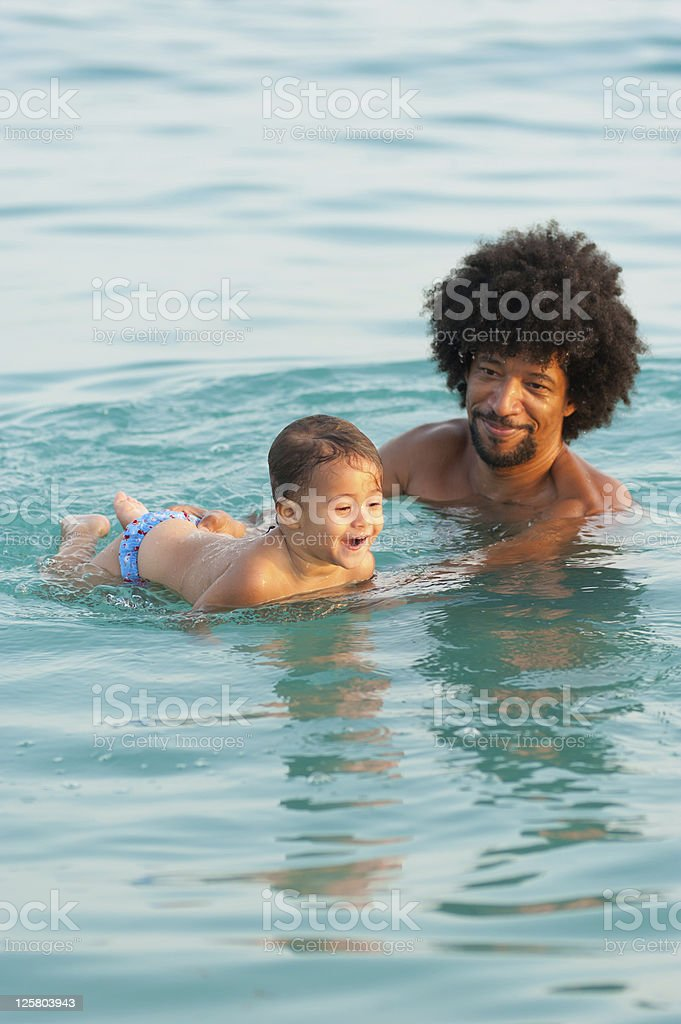 Father helping his young son swim in open water stock photo