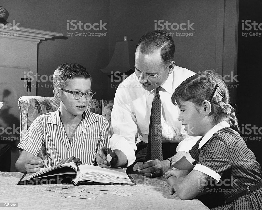 Father helping son and daughter with homework royalty free stockfoto