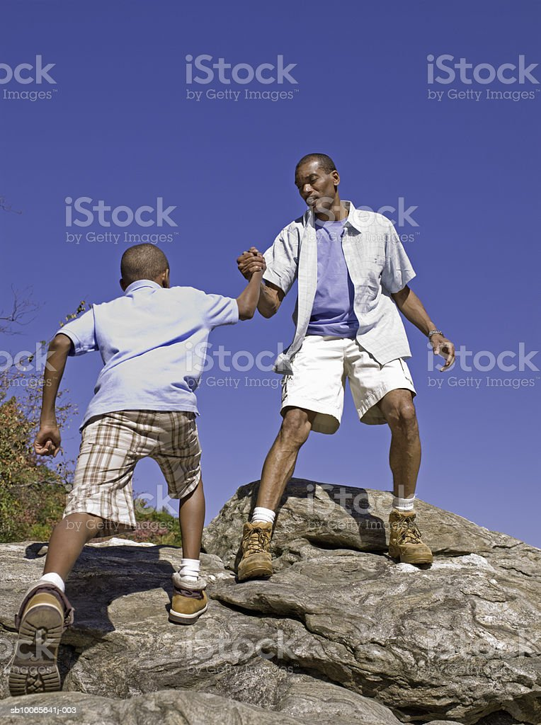 Father helping son (12-13) in climbing rock, low angle view royalty-free stock photo
