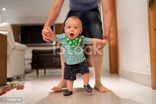 Father helping son learn to walk at home