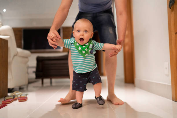 Father helping son learn to walk at home stock photo