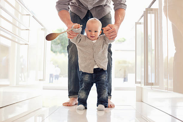 father helping son learn to walk - first step stock photos and pictures