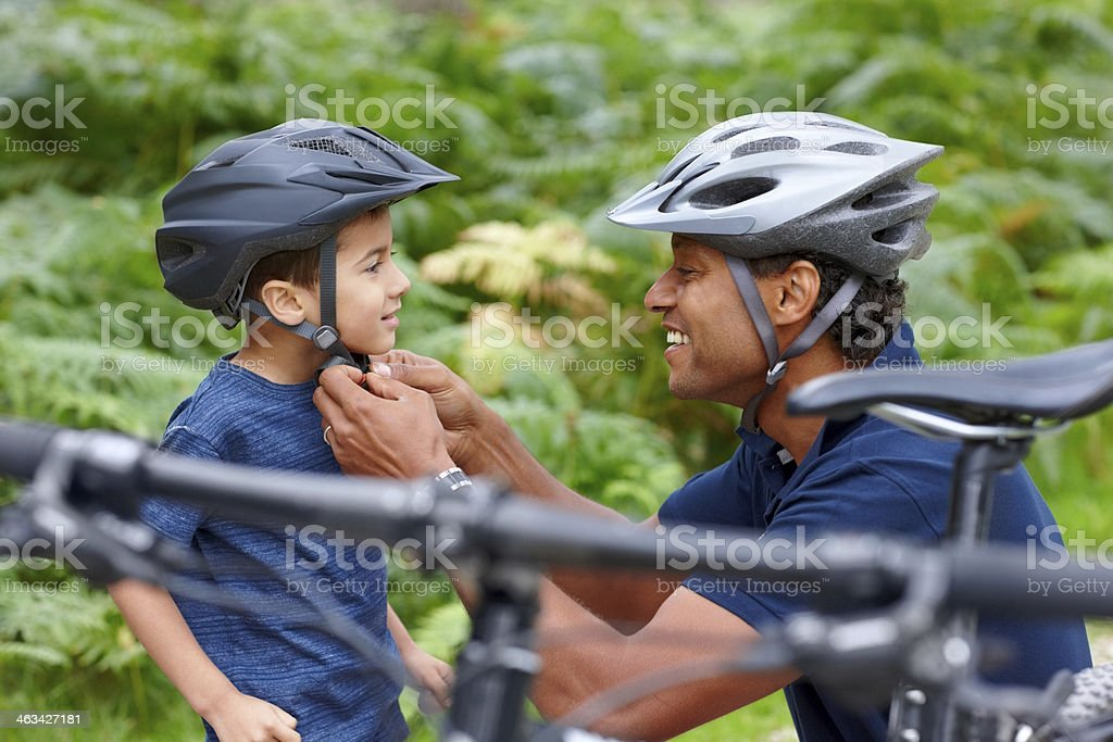 Father helping son put on helmet stock photo