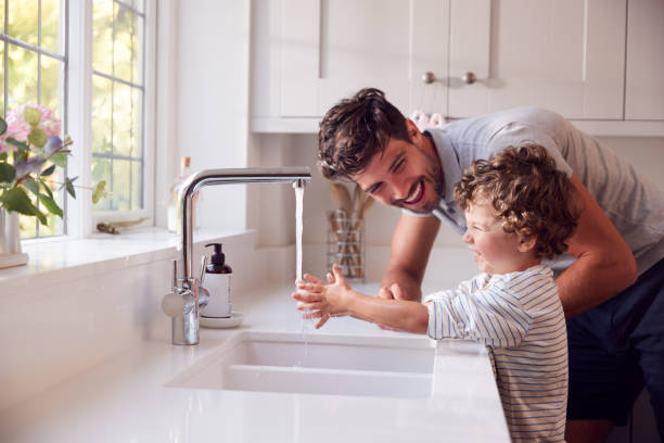 Father Helping Son To Wash Hands With Soap At Home To Stop Spread Of Infection In Health Pandemic stock photo
