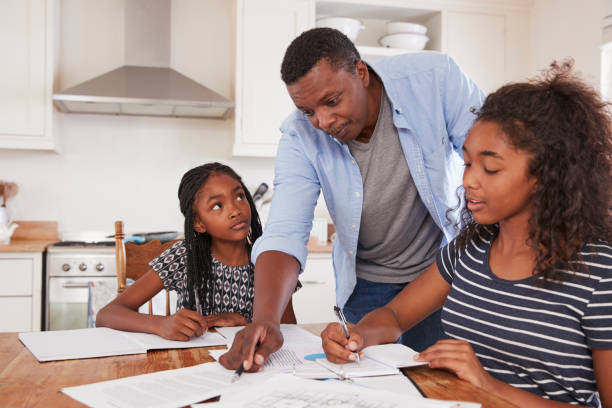 Father Helping Two Daughters Sitting At Table Doing Homework stock photo