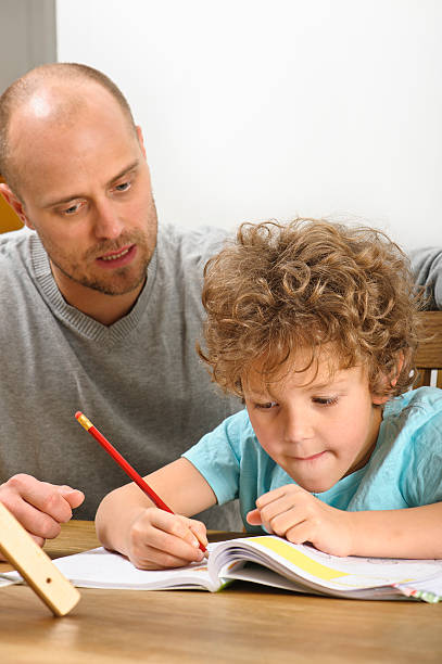 father helping with homework stock photo