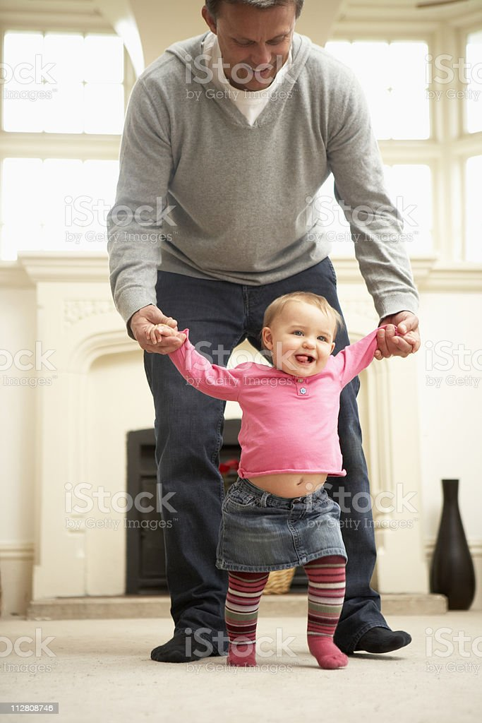Father Helps Baby Daughter With Walking royalty-free stock photo
