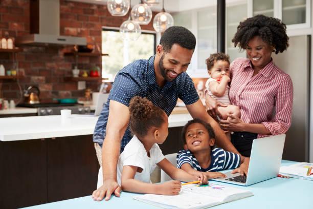 아버지는 어머니는 아기를 보유 하는 동안 아이 들 숙제를 도움이 됩니다. - 5명 뉴스 사진 이미지