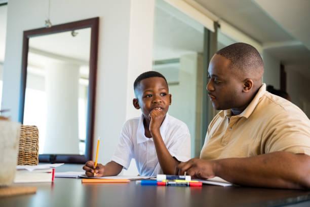 Vater hilft ihrem Sohn bei seinen Hausaufgaben – Foto