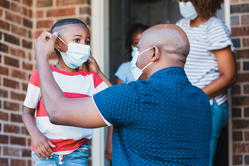 A mid adult father helps his young son put on a protective face mask before leaving their home amid the coronavirus pandemic.