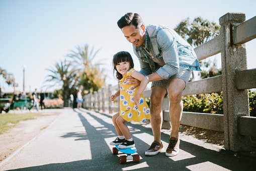 A dad helps his little girl go skateboarding, holding her waist for support.  Shot in Los Angeles, California by the Santa Monica Pier.
