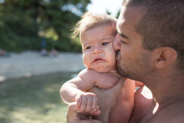 Father holding and kissing a crying baby stock photo