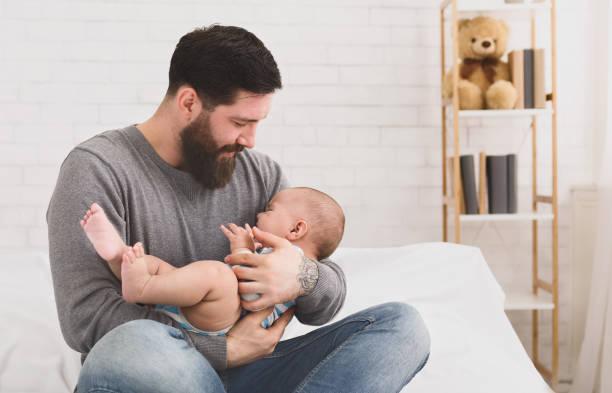 vater holding und beruhigende schreiendes neugeborenes baby im arm - genderblend stock-fotos und bilder