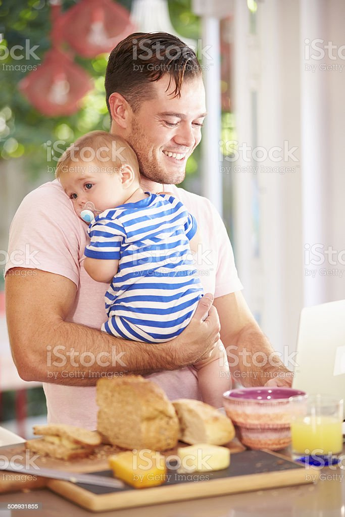 Father Holding Baby And Making Snack Whilst Using Laptop stock photo