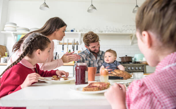 Father holding baby boy at breakfast table, mother clapping and entertaining him stock photo