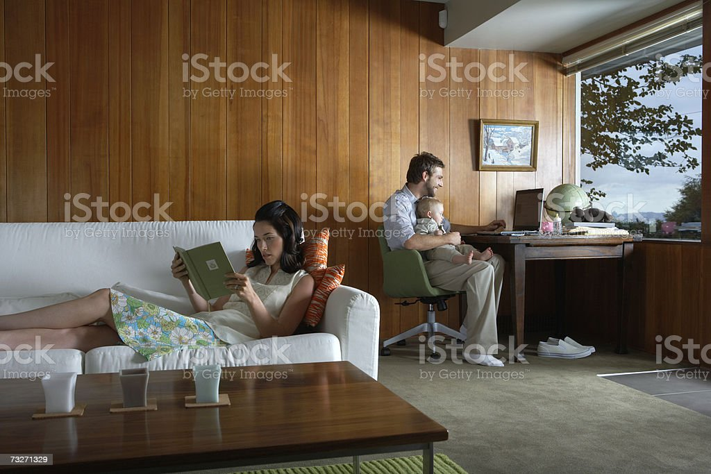 Father holding baby girl (6-9 months) while mother reads in living room royalty-free stock photo