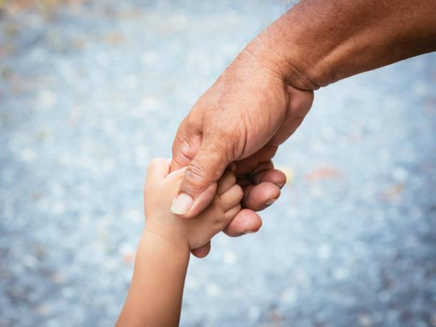 Vater hält Baby HandFinger und Farbe Ton Effekt – Foto