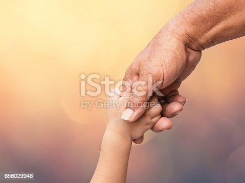 Father holding baby hand finger on blurred bokeh background