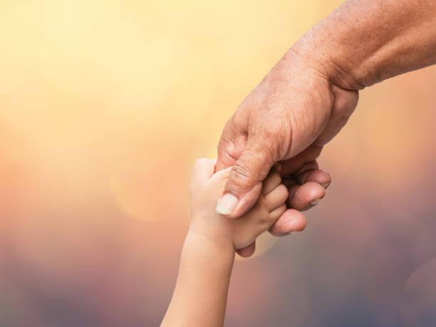 Vater hält Baby Handfinger auf verschwommenen Bokeh Hintergrund – Foto