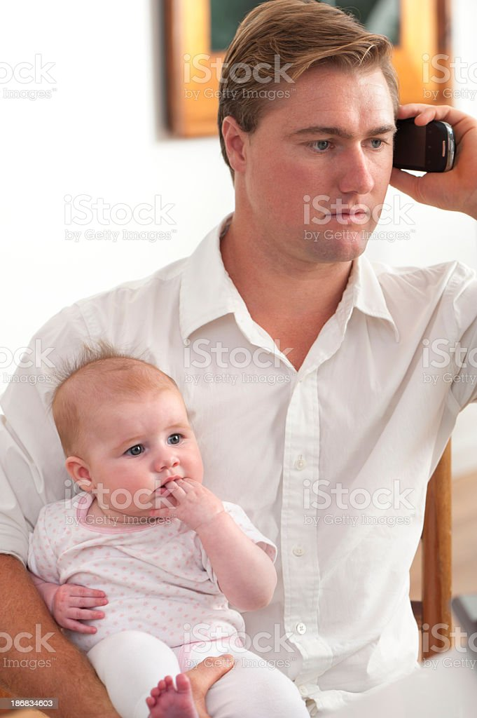 Father holding baby while on the phone royalty-free stock photo