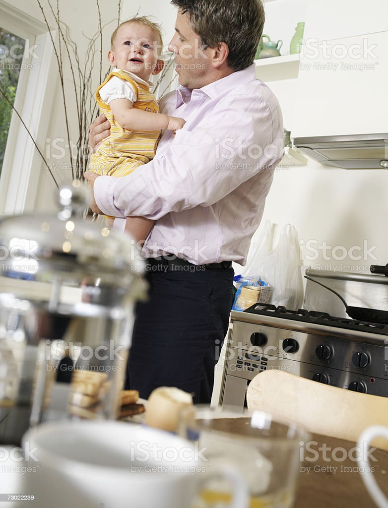 Father holding daughter (9-12 months) in kitchen royalty-free stock photo