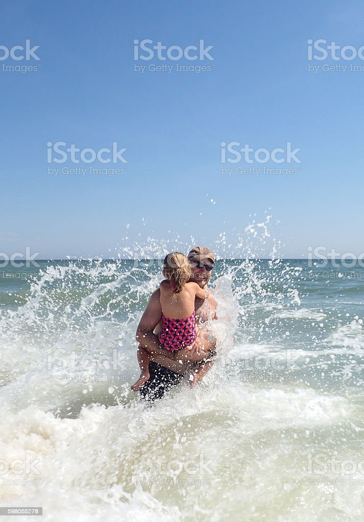 Father holding daughter in surf at Bethany Beach, Delaware stock photo
