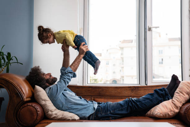 Father Holding Daughter In The Air stock photo