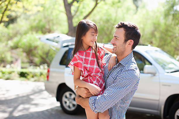 Father holding daughter outdoors stock photo