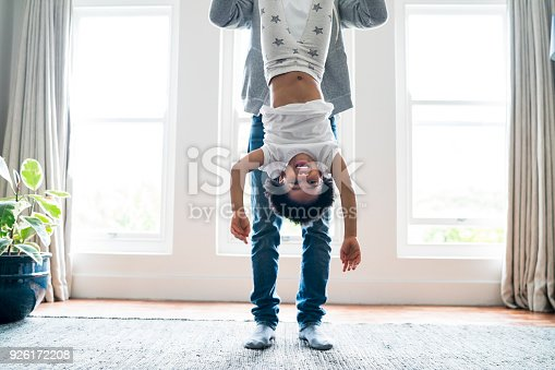 Low section of father holding daughter upside down at home. Portrait of happy girl enjoying against windows. They are wearing casuals.