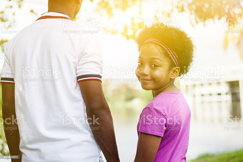 Father holding hands of daughter - African American family stock photo