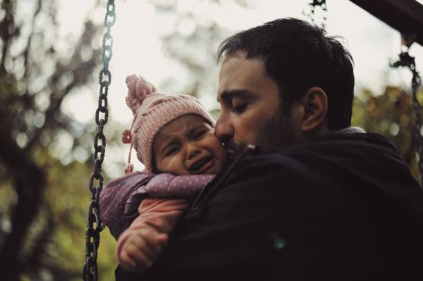 Father holding his 1 year old baby girl at a park stock photo