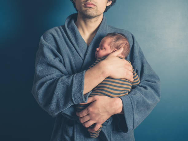 Father holding his baby son A young father wearing a bathrobe is holding his baby son stay at home father stock pictures, royalty-free photos & images