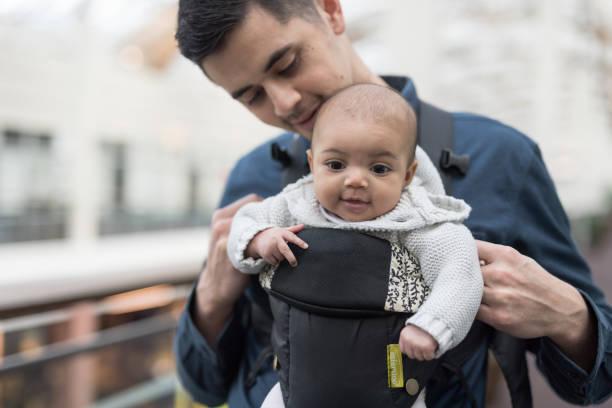 padre con su hija en un portabebé en un centro comercial - intergénero fotografías e imágenes de stock