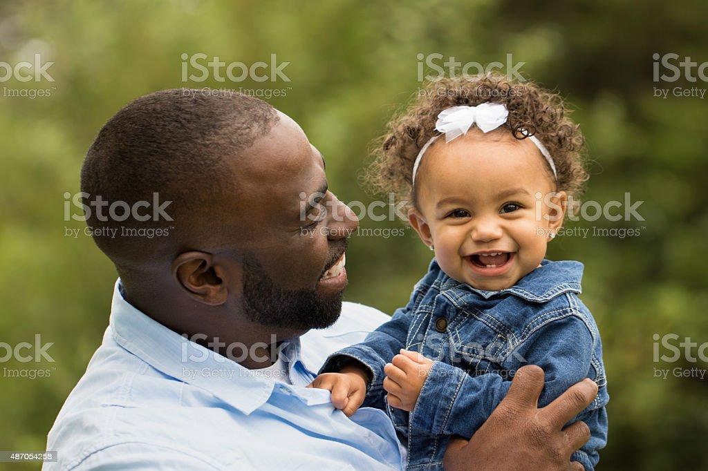 Padre sostiene a su niña. - foto de stock