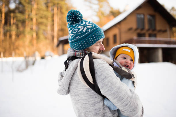 Father holding his son in baby carrier. Sunny winter nature. stock photo