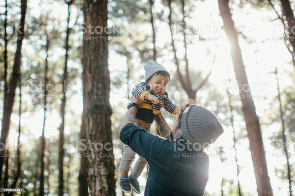 Father holding his son in forest in sunset. stock photo